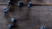 mirtilos : Blueberries rolling on a wooden board. Slow motion. Stock Footage