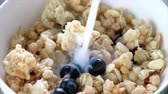 müsli : Pouring milk into a bowl of cereals and blueberry fruits