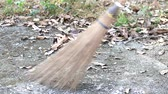 çim : Sweeping dry leaves with coconut-palm leaf stalk broom on concrete floor