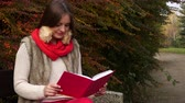 literatuur : Woman fashion girl relaxing in autumnal park reading book sitting on bench. Fall lifestyle concept. 4K ProRes HQ codec Stockvideo