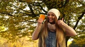 witamina c : Woman holding pills tablets in autumn fall park forest. Young girl in jacket and scarf giving thumb up gesture. Health care. 4K ProRes HQ codec.