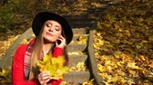 меланхолия : Woman relaxing in autumn fall park steadicam. Young girl in hat holding leaves sitting on stairs. 4K ProRes HQ codec.