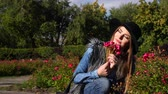 rose garden : Woman smelling red rose flowers in park. Fashionable girl in hat relaxing outdoor enjoying nature sunlight 4K. Prores HQ codec