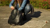 questões : Woman in fashionable clothes with handbag looking for something. 4K ProRes HQ codec Stock Footage