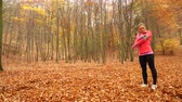 스트레칭 : Woman warming up in autumn fall park forest. Young girl with smartphone armband activity tracker. Fitness technology. 4K steadicam shot ProRes HQ codec.