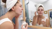 bálsamo : Woman applying facial moisturizing mask on face looking in mirror. Girl taking care of her complexion layering moisturizer. Skincare spa treatment. 4K ProRes HQ codec