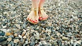 педикюр : Woman feet wearing sandals on stone beach Стоковые видеозаписи
