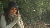 coldness : Woman outdoor. Fashionable autumn girl with long hair in black hat walking on nature. Beauty female model in the park warming her hands 4K Prores HQ codec Stock Footage