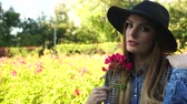 ruiken : Woman holding red rose flowers in park. Fashionable girl in hat relaxing outdoor enjoying nature 4K. Prores HQ codec Stockvideo