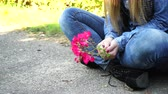 меланхолия : Woman hands holding red rose flowers outdoor. Girl wearing denim trousers sitting on the ground in park 4K Prores HQ codec