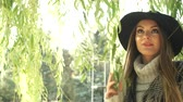 salgueiro : Woman outdoor. Fashionable autumn girl long hair wearing fur vest black hat enjoy nature. Beauty female model relaxing in park. 4K