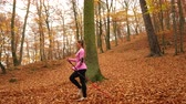 yürüteç : Woman doing nordic walking in autumn park forest with smartphone app. Active girl with activity tracker armband. Fitness technology. 4K steadicam shot ProRes HQ codec.
