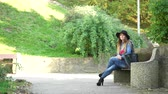 меланхолия : Woman outdoor. Fashionable autumn girl with long hair wearing black hat sitting on bench and waiting for someone, 4K. Prores HQ codec