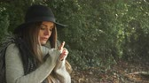 ısınma : Woman outdoor. Fashionable autumn girl with long hair in black hat walking on nature. Beauty female model in the park warming her hands 4K Prores HQ codec Stok Video