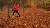hajlítás : Woman warming up in autumn fall park forest. Young girl with smartphone armband activity tracker. Fitness technology. 4K ProRes HQ codec.