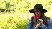 cheiro : Woman holding red rose flowers in park. Fashionable girl in hat relaxing outdoor enjoying nature 4K. Prores HQ codec Stock Footage