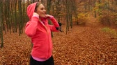 jogging yapan : Woman runner jogger in autumn park fall forest with smartphone app. Young girl with activity tracker armband. Fitness technology. 4K steadicam shot ProRes HQ codec.