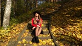 меланхолия : Woman relaxing in autumn fall park steadicam. Young pensive girl in hat sitting on stairs. 4K steadicam shot ProRes HQ codec.
