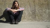 nezaměstnaný : Man with long hair sitting by grunge wall outdoor. Unemployment depression or abuse concept 4K