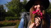 vonící : Woman holding red rose flowers in park. Fashionable girl in hat relaxing outdoor enjoying nature 4K. Prores HQ codec Dostupné videozáznamy