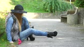 меланхолия : Woman sad outdoor. Fashionable autumn girl wearing black hat sitting in the park and waiting for someone parkland after 4K. Prores HQ codec