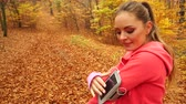бегун : Woman running jogging in autumn park fall forest setting smartphone app. Young girl with activity tracker armband. Fitness technology. 4K steadicam shot ProRes HQ codec. Стоковые видеозаписи
