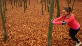 pressione : Woman warming up in autumn fall park forest. Young girl with smartphone armband activity tracker. Fitness technology. 4K steadicam shot ProRes HQ codec.