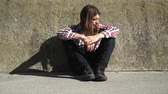 corte : Man with long hair sitting by grunge wall outdoor. Unemployment depression or abuse concept. 4K