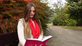 bank : Woman fashion girl relaxing in autumnal park reading book sitting on bench. Fall lifestyle concept. 4K steadicam shot ProRes HQ codec Stok Video