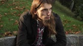 corte : A man with long hair on a bench in autumnal park 4K with motorized slider ProRes HQ codec