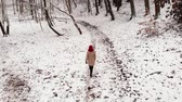 Woman walk in winter snowy forest.