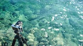 hobiler : Photo camera on sea shore and clear water Stok Video