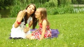 soap bubbles : Summer. Mother with little daughter having fun. Young woman and girl child blowing soap bubbles outdoor. Stock Footage