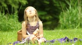 Summer picnic. Little girl eating sandwich breakfast meal. Child kid relaxing on the meadow or in the park. Stock Footage