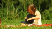 электроника : Summer. Little girl child kid in sunglasses using a tablet on the meadow. Outdoor. Mobile technology.