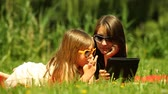 čtenář : Summer picnic. Young woman with little girl in sunglasses using tablet on the meadow. Child kid eating bar. Mobile technology.