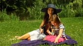 Summer picnic. Mother and baby girl in a straw hat.