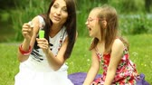 Summer. Mother with daughter having fun. Young woman and girl child blowing soap bubbles on the meadow.