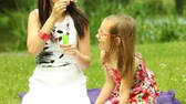 brinquedos : Summer. Mother with little daughter having fun. Young woman and girl child blowing soap bubbles outdoor. Vídeos