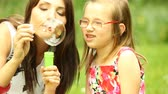 brinquedos : Summer. Mother with daughter having fun. Young woman and girl child blowing soap bubbles on the meadow.