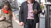 woman and man holding hands walking with mobile phones in the city