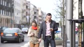woman and man holding hands using mobile phone outside in street. Young urban couple hanging out in the city.