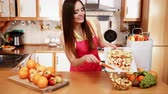 súly : Woman young housewife in kitchen at home slicing apple on cutting board and throwing fruits into bowl. Healthy eating, cooking, vegetarian food, dieting and people concept. 4K ProRes HQ codec