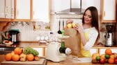 extractor : Woman young housewife in kitchen with fruits and juicer preparing to make fresh juice. Healthy eating, cooking, vegetarian food, dieting and people concept. 4K ProRes HQ codec