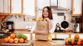 vegetarianismo : Woman young housewife in kitchen holding grocery shopping bag, many fruits on counter. Healthy eating, cooking, vegetarian food, dieting and people concept. 4K ProRes HQ codec