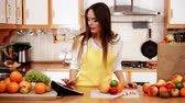 かんきつ類の果実 : Woman young housewife in kitchen with many fruits on counter using tablet looking at recipes. Healthy eating, cooking, vegetarian food, dieting and technology concept. 4K ProRes HQ codec