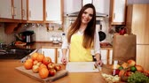 нож : Woman young housewife in kitchen at home slicing apple on cutting board and throwing fruits into bowl. Healthy eating, cooking, vegetarian food, dieting and people concept. 4K ProRes HQ codec
