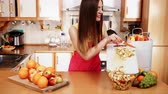 saláta : Woman young housewife in kitchen at home slicing apple on cutting board and throwing fruits into bowl. Healthy eating, cooking, vegetarian food, dieting and people concept. 4K ProRes HQ codec