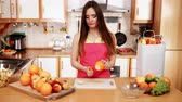 saláta : Woman young housewife in kitchen at home peeling orange fruit for salad or juicing. Healthy eating, cooking, raw food, dieting and people concept. 4K ProRes HQ codec