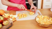 потеря в весе : Woman young housewife in kitchen at home slicing fresh orange fruits on cutting board for salad or juicing. Healthy eating, cooking, raw food, dieting and people concept. 4K ProRes HQ codec